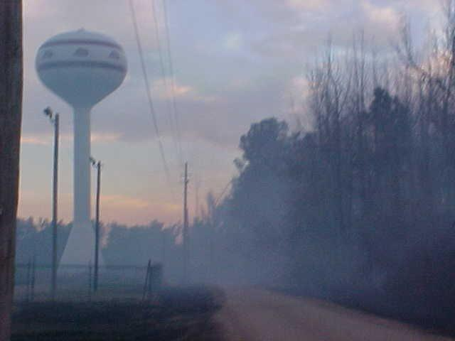 Smoke rises in front of a water tower.