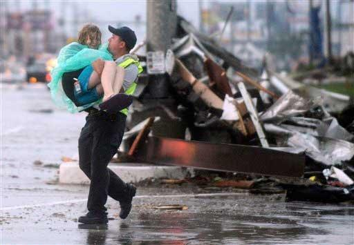 Emergency worker carries victim from danger.