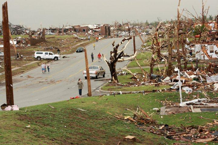 Entire city block bulldozed by the tornado, trees left splintered.