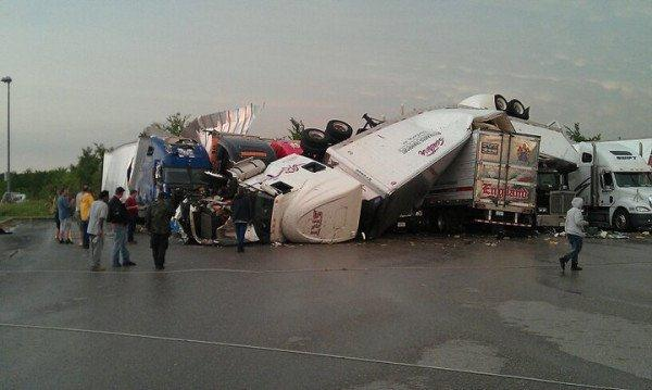 Semi-Trucks thrown like toys in the storm, piled on top one another.