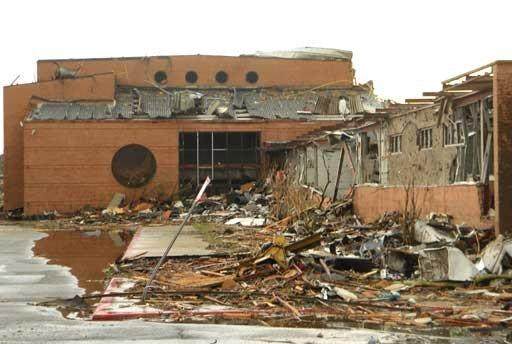 Building severely damaged by the tornado, extensive wall damage.