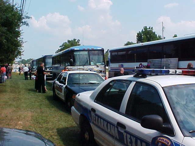 Police cruisers sit in front of the buses.