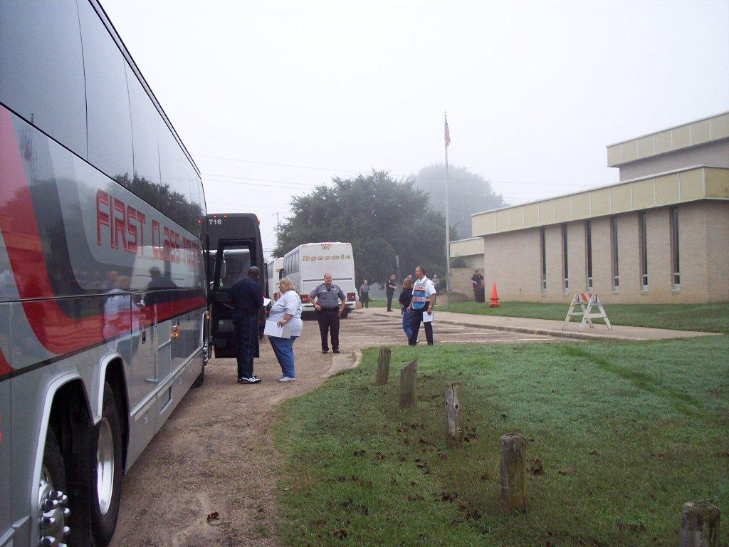 The buses to the shelter arrive, and are greeted by emergency personnel.