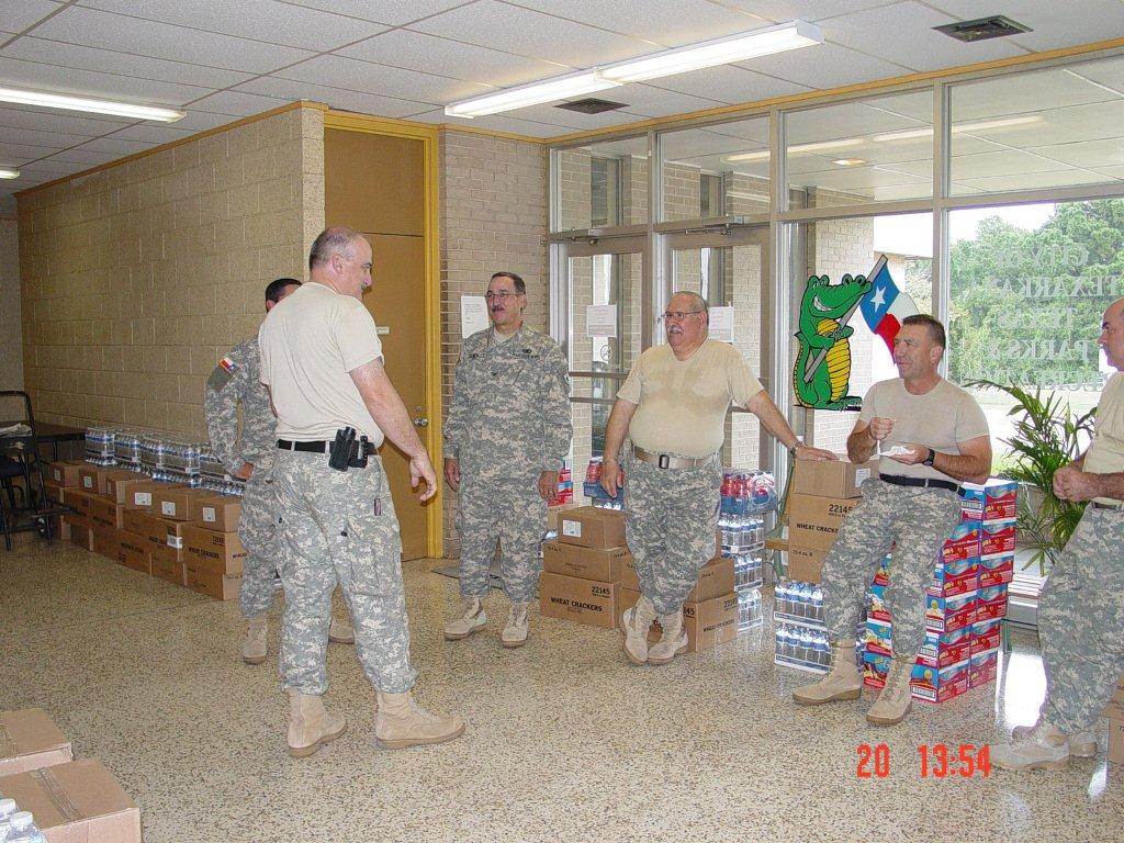 Military personnel standing near supplies in the shelter.