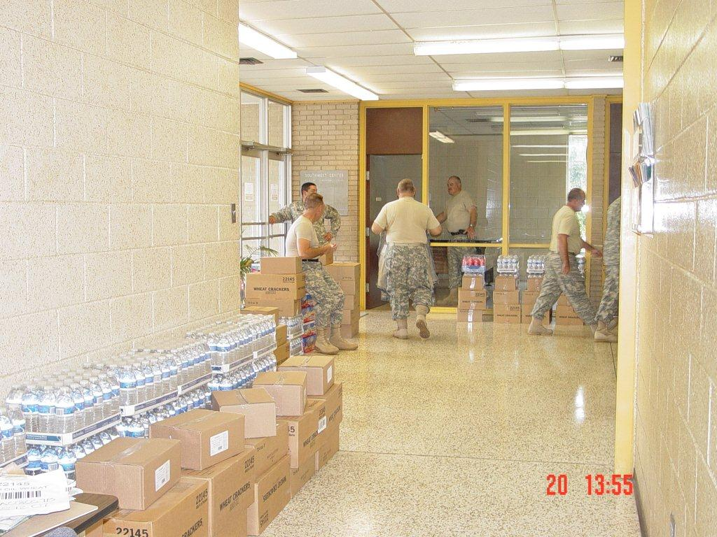 Military personnel set up water and food for the shelter.