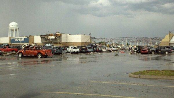 Parking lot outside damaged Walmart store, cars have been pushed into one another, or tossed on top of others.