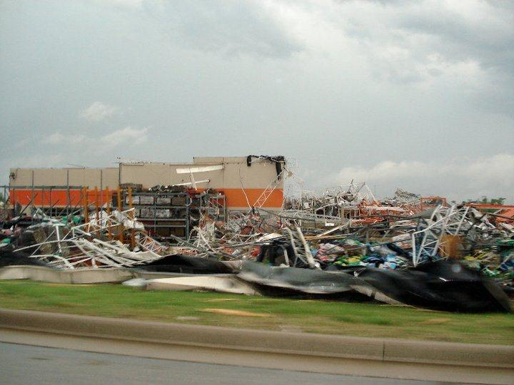 Debris from the tornado covers a street block, damaged building in the background.